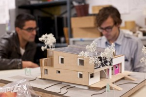 Photo of a model of Empowerhouse. Two students work in the background.