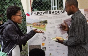 Photo of two people talking in front of an Empowerhouse sign.