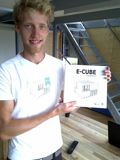 "Photo of a man holding a book titled ""E-Cube."""