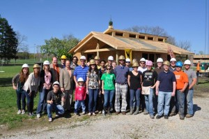Photo of a group of people wearing hardhats in front of a partially constructed house.
