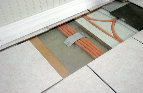 Photo of a section of tiled floor that has been removed to reveal radiant heating tubes below.