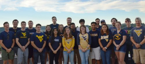 Photo of the Solar Decathlon 2017 team from West Virginia University; they are a group of about 20 students, men and women, smiling and wearing various designs of blue and gold WVU t-shirts. A skyline featuring a ridge of Appalachian Mountains is in the background.