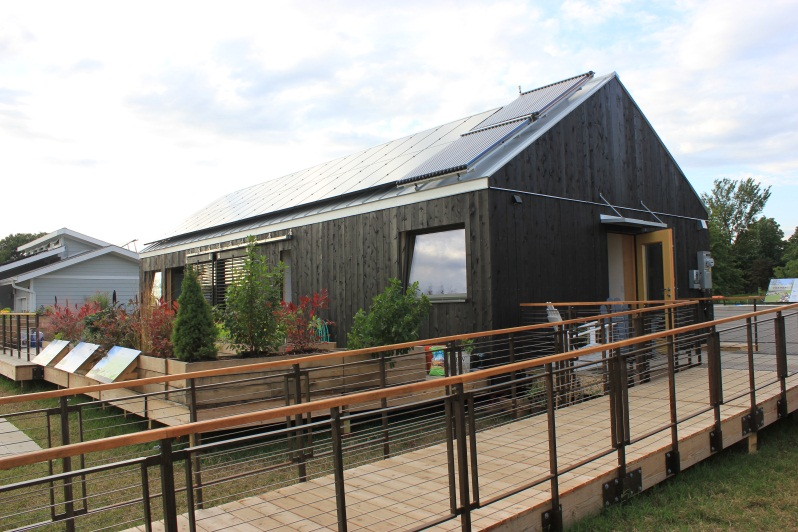 Photo of a wooden house with PV panels and a solar hot water system on the roof.