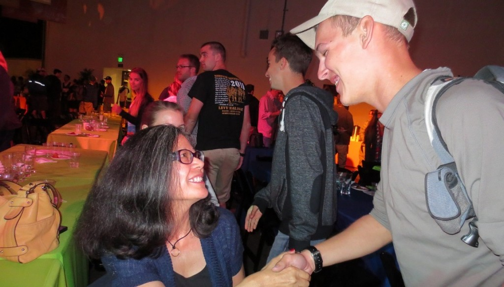 Photo of Vivian Stafford shaking the hand of a Norwich University student at a reception.