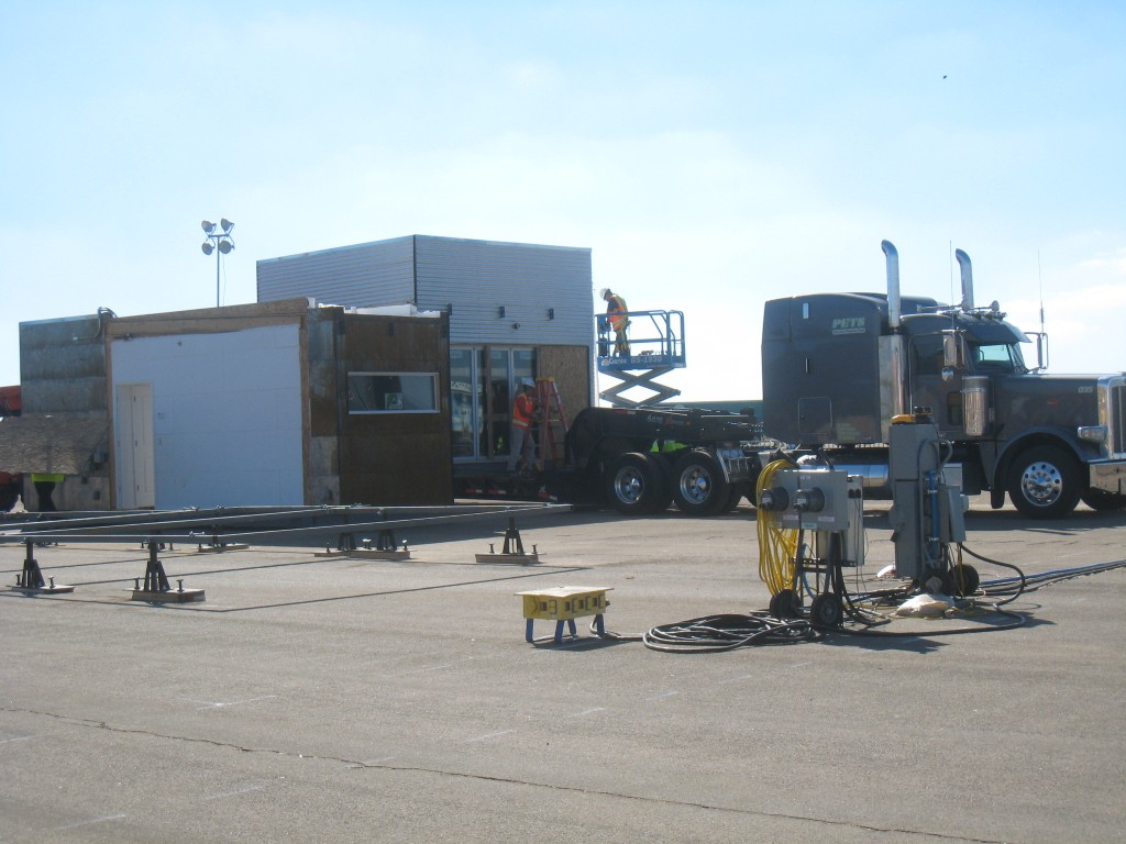 Photo of a diesel offloading a segment of the Team Texas house.