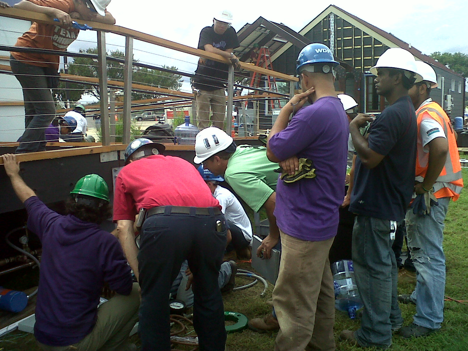 Photo of team members surrounding the building inspector as he looks underneath the deck of a house.