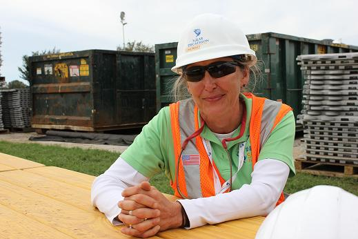 Photo of a woman wearing safety glasses, hard hat, and vest.