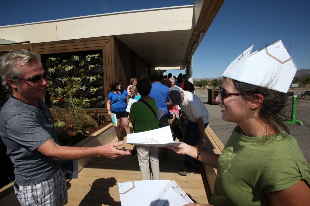 Photo of Sandra Violand distributing handouts to visitors in line at the LISI house.