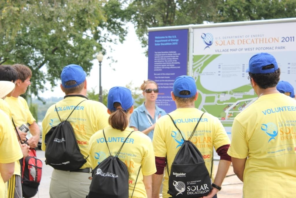 Photo of several volunteers gathered around a map of the solar village.