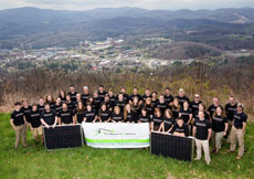 "Photo of a group of people in matching shirts standing on a hill overlooking a campus. In front, the team holds two PV panels and a sign that says ""The Solar Homestead: Appalachian State University. Appalachian State Solar Decathlon Headquarters."""