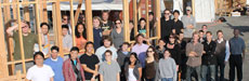 Photo of the Southern California Institute of Architecture and California Institute of Technology Solar Decathlon team members standing in within and in front of a framed structure.