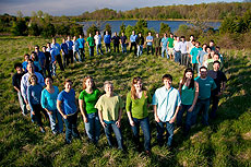 Photo of a group of people standing in a circle in a field. In the background is a body of water.