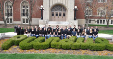 "Photo of the Purdue University team members in front of a building on campus. In front of them is a hedge cut to read ""Purdue."""