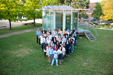 Photo of a group of people standing in a V shape in front of a glass building with PV panels.