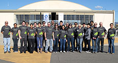 Photo of the Arizona State University and The  University of New Mexico Solar Decathlon 2013 team standing in front of an  airplane hangar.
