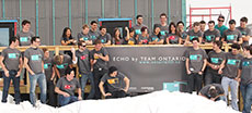 Photo of members of the Queen's University, Carleton  University, and Algonquin College Solar Decathlon 2013 team on the deck of  their partially constructed house. Several members are laughing and throwing  snowballs.