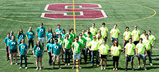 Photo of members of the Stevens Institute of Technology  Solar Decathlon 2013 team standing on an athletic field marked with the letter  S.