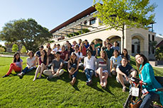 Photo of members of the Stanford University Solar  Decathlon 2013 team on a small hill in front of a campus building.